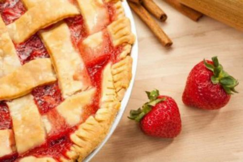 side view of rhubarb pie with strawberries and cinnamon sticks on light wood table top