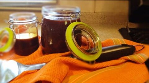 barbecue sauce in two glass mason jars, one with a green rubber sealing ring, on an orange tea towel and a bbq spatula alongside