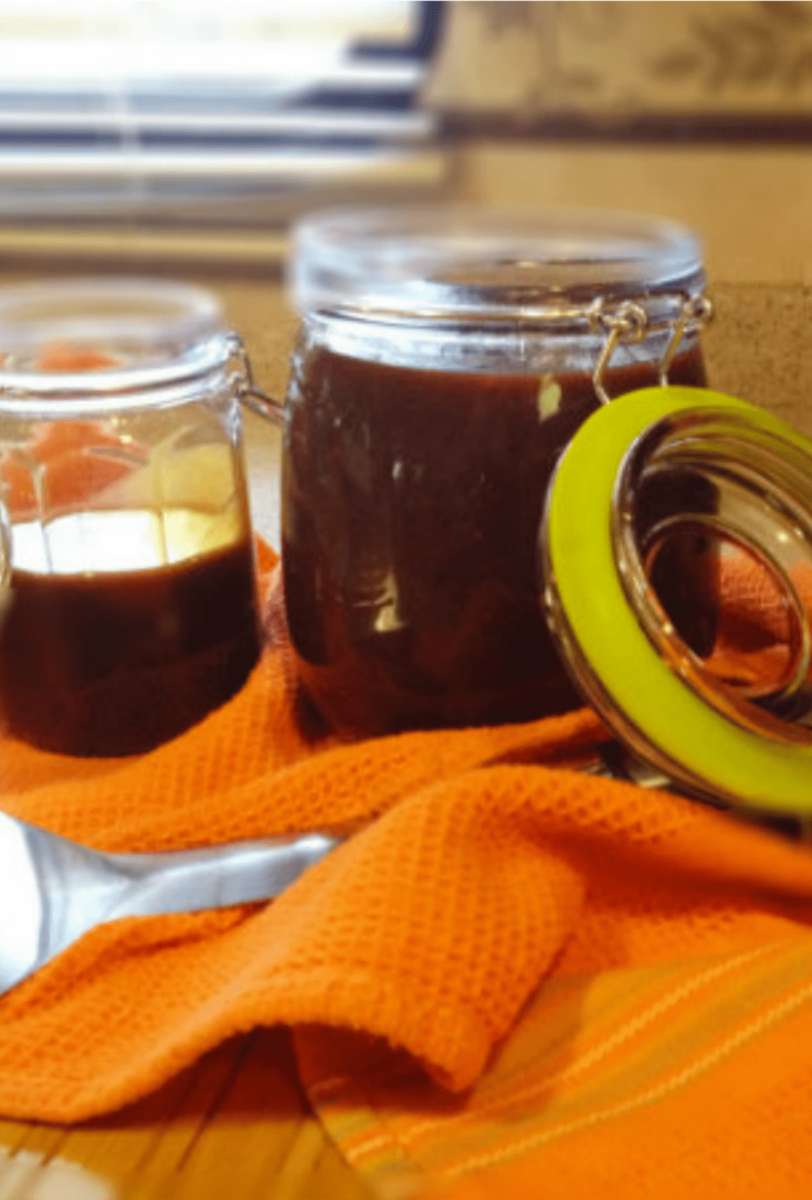 closeup image of two jars of homemade bbq sauce in glass jars