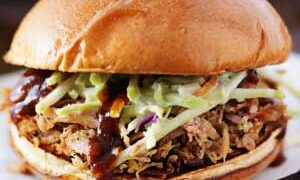 pulled pork on crusty bun with coleslaw and bbq sauce