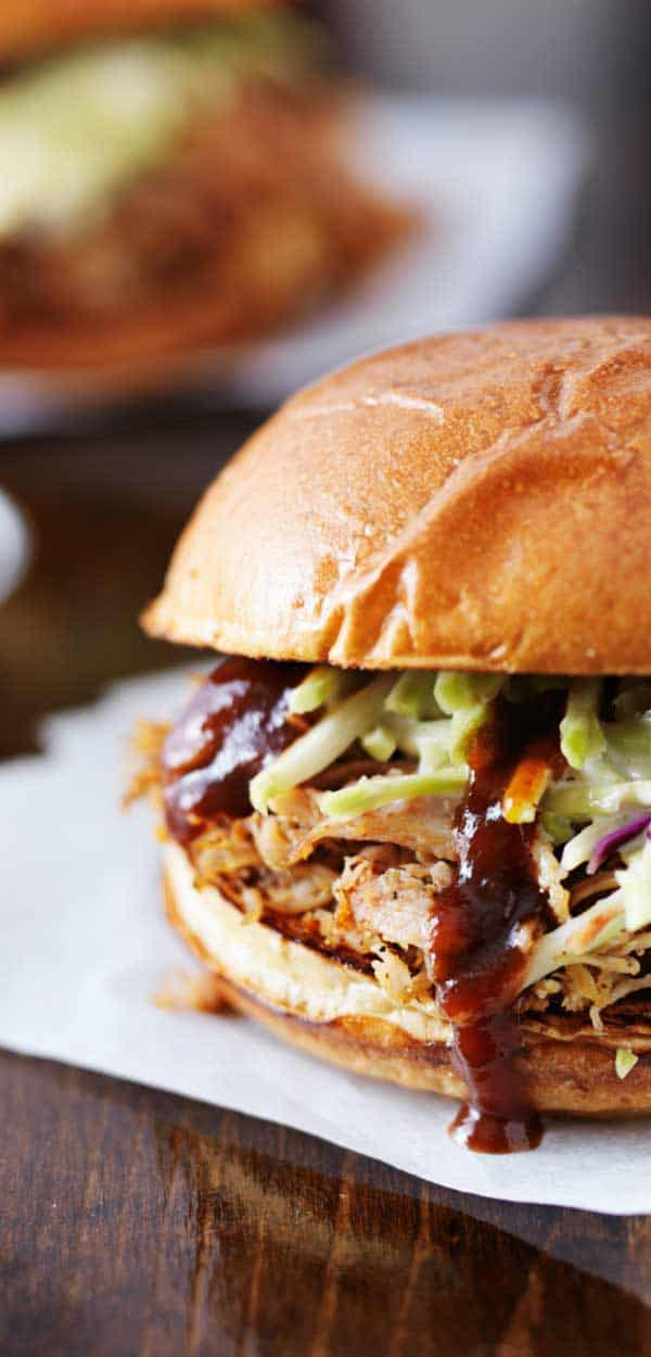 This is the best slow cooker pulled pork shoulder recipe ever with homemade BBQ sauce! Add some coleslaw, corn on the cob and dessert to complete this easy meal.