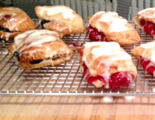 several blueberry and cherry hand pies with sugar glaze, cooling on a baker's rack