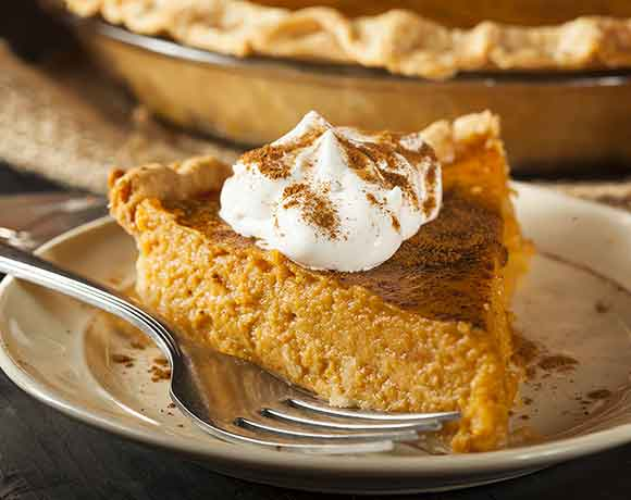 slice of homemade pumpkin pie with fork on a white plate, topped with whipped cream and pumpkin pie spice