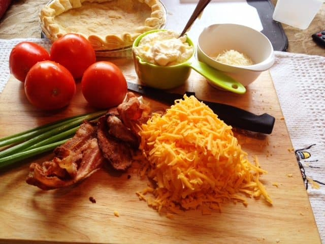 ingredients for tomato pie, tomatoes, pie crust, mayonnaise, green onions, bacon and shredded cheese on a cutting board