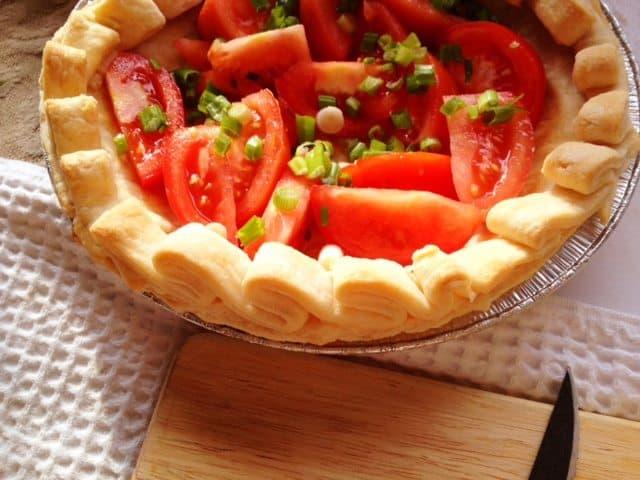 tomato pie with ribbon edged pie crust ready to bake