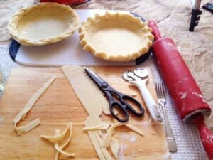 2 pie crust shells one with fluted edge and one with braided edge, cutting board, kitchen scissors, pie crust scraps, pastry wheel and rolling pin
