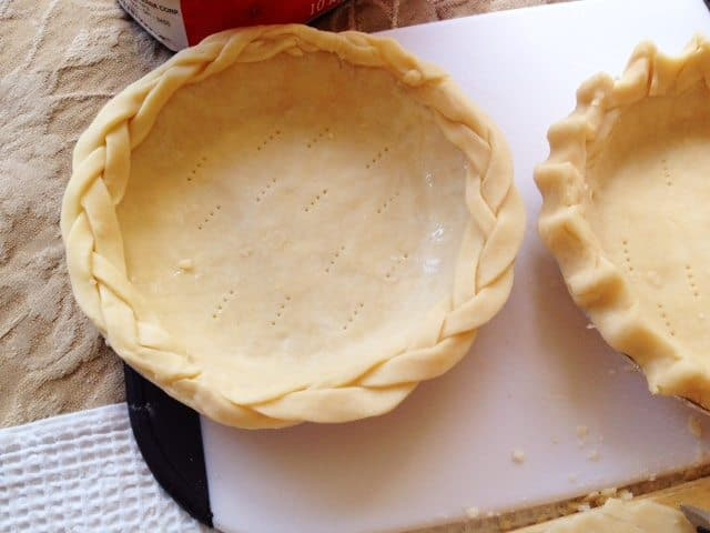 Two types of pie crust edging, braided and fluted, ready to go into the oven