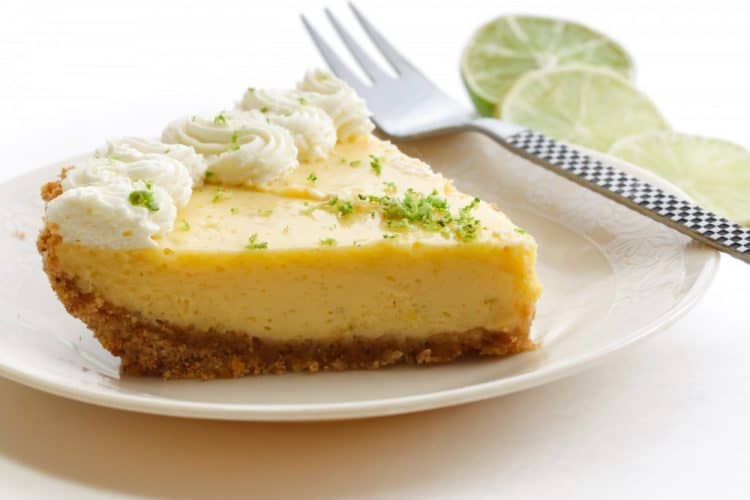 slice of Key lime pie on a white plate with whipped cream and a fork, slices of key limes in the background
