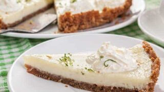 key lime pie side view slice of lime on top with slice of pie on white plate, easy key lime pie recipe