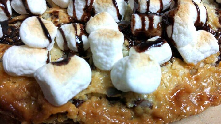 close up of baked magic cookie bar pizza shows toasted marshmallows, chocolate sauce on the cookie bar base