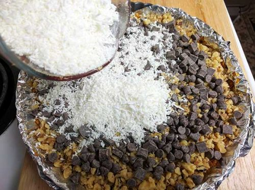 layering the coconut flakes on top of the chocolate chips for the seven layer bar or magic cookie bar recipe