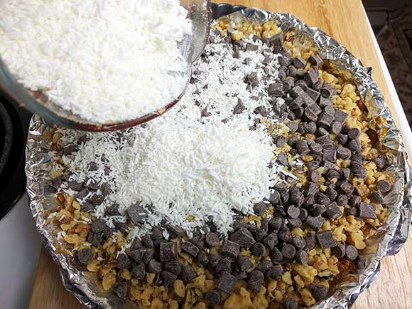 This magic cookie bar recipe becomes an All Dressed Dessert Pizza! The ooey gooey combination of chocolate, coconut, and graham crackers topped with a thick layer of sweetened condensed milk – oh wow!  Just like a S'mores Magic Cookie Bar Dessert Pizza! You know what I mean!