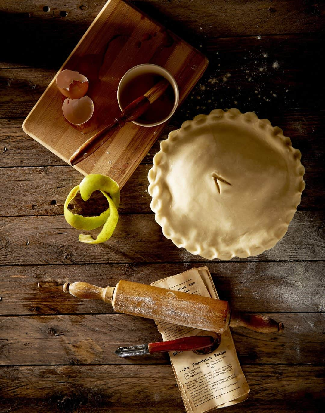 apple pie ready to be baked on a wooden counter with rolling pin, and baking utensils