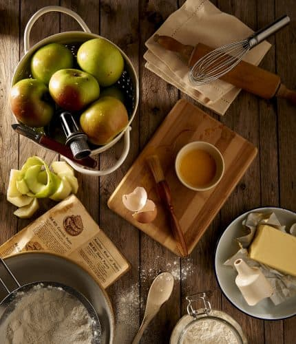 a flatlay of items needed to make an apple pie colander of apples mixing spoons butter flour cutting board cinnamon all on a wooden countertop