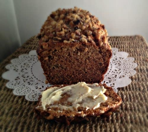 banana bread with one slice buttered in foreground