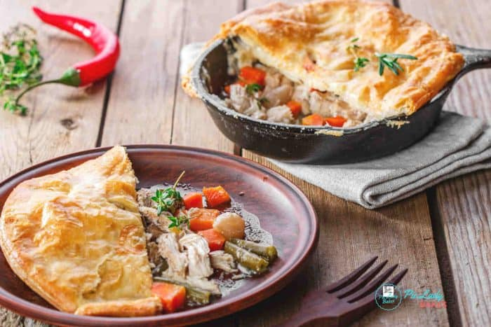 Facebook image Chicken Pot Pie with puff pastry crust on a brown plate with brown fork, shows cast iron skillet in background with serving removed, and red chili pepper to the left