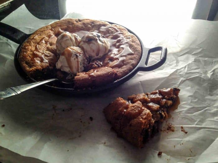 homemade chocolate chip skillet cookie fresh from the oven, slice waiting on parchment paper