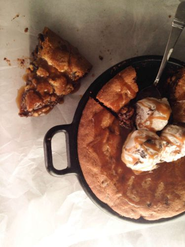 homemade chocolate chip skillet cookie overhead shot, topped with ice cream and slice top left