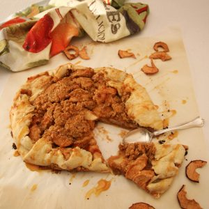 apple galette, with slice and spoon on parchment paper