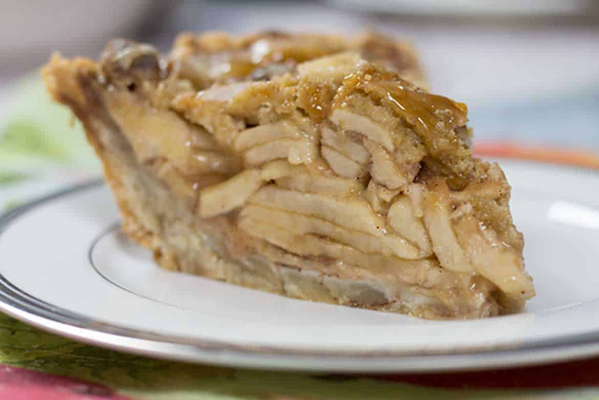 close up image of a slice of dutch apple pie on a white plate