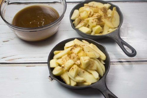 glass bowl with caramel sauce and two small cast iron skillets with sliced apples in them