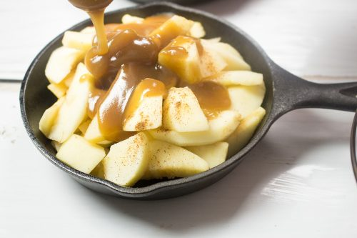 sliced apples with cinnamon, and caramel filling pouring on apples in a small black cast iron skillet