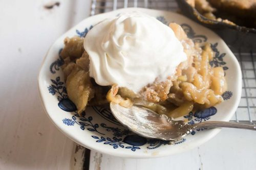 old fashioned apple pandowdy with whipped cream on a delft blue saucer & antique spoon