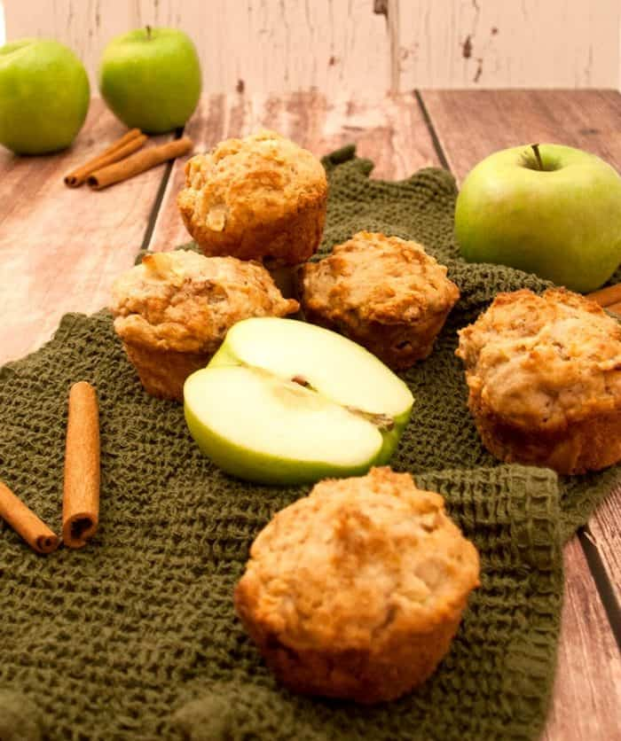 freshly baked apple muffins on a tea towel with granny smith apples and cinnamon sticks