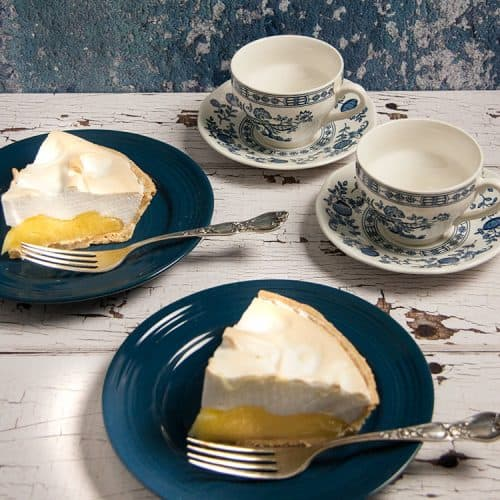 two slices of lemon meringue pie on blue plates with silver forks two cups and saucers