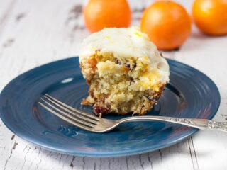 generous slice of orange cranberry pound cake on a dark blue plate with vintage silver fork, two oranges in background on a weathered white wooden counter