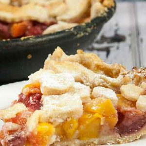 You will love this Homemade Peach Mango Sangria Skillet Pie, full of everything you put in Sangria, it's a burst of summertime right in your mouth. Skillet pies are so much fun to bake, and this easy peach mango pie recipe is no exception!