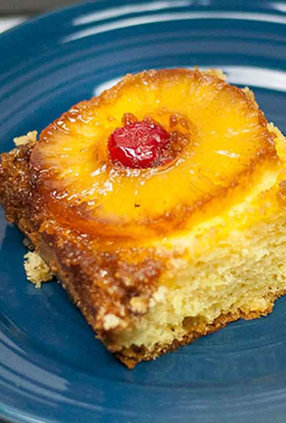 serving of yellow cake with pineapple slice and cherry baked on top on a blue dessert plate