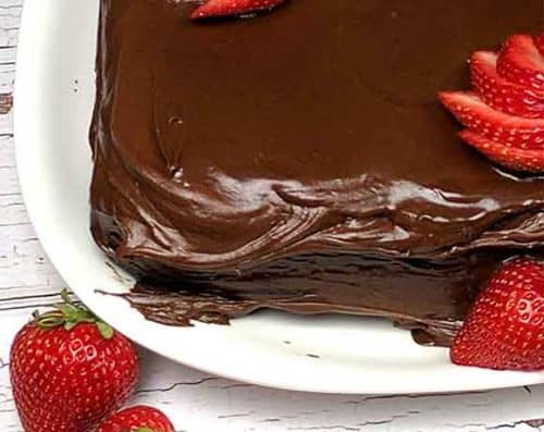 square chocolate cake corner with sliced strawberries on a white square plate