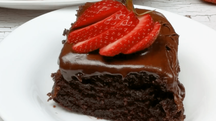 small piece of chocolate cake on a white plate with a sliced strawberry fanned on top of chocolate buttercream icing