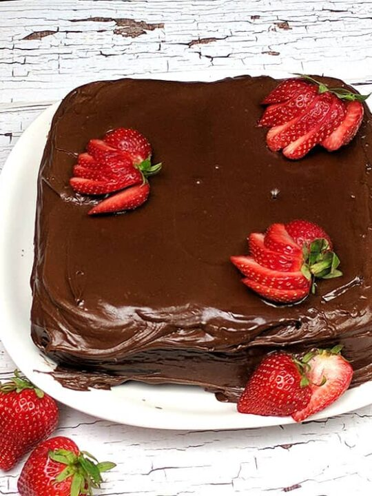 hocolate Mayonnaise Cake square on a white plate on white wooden table with sliced strawberries arranged on top and side