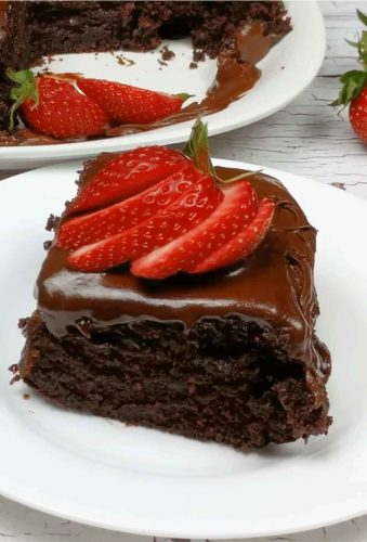 Slice of chocolate cake with sliced strawberries on top shown on white plate with whole cake in background