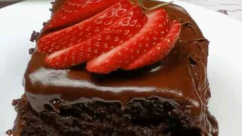 slice of chocolate cake on a white plate with sliced strawberries on top of chocolate frosting with whole cake in background