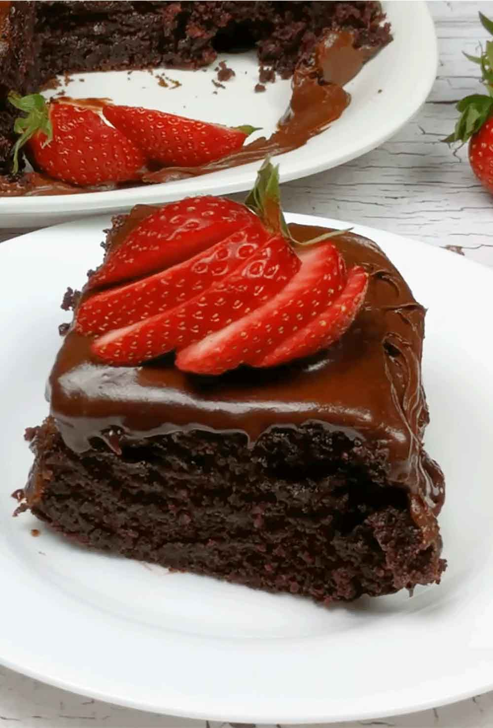 Slice of chocolate mayonnaise cake with sliced strawberies on top shown on white plate with whole cake in background