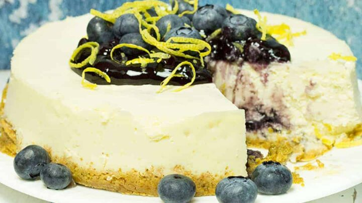 lemon blueberry cheesecake on white plate with blueberries and lemon peel piled on top, blueberries on the side, and a slice removed. shows a blue background on top of a white wooden table