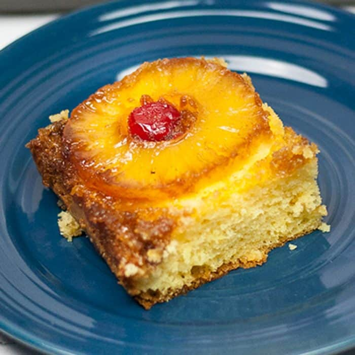 piece of pineapple upside down cake on blue plate with slice of pineapple and maraschino cherry on top, box cake mix hacks