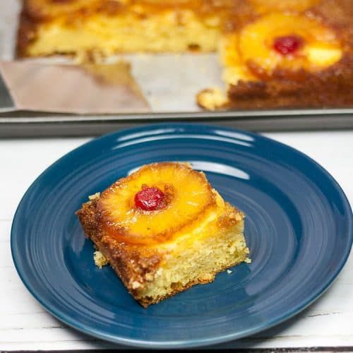 pineapple upside down cake with slice of pineapple and cherry on top on a blue plate with rest of cake in pan in the background