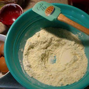 blue mixing bowl, with spatula and cake mix in bowl, getting ready to bake italian almond biscotti