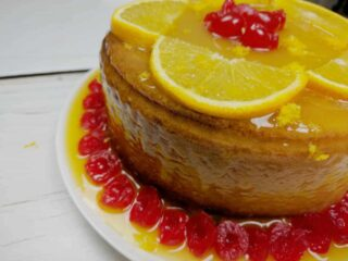 side view of harvey wallbanger cake, a yellow cake with orange glaze, orange slices on top with maraschino cherries in the middle and all around the base of the cake which is on a white plate