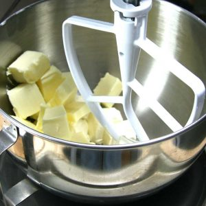 mixing the butter and cream cheese in stainless steel bowl with white beater blade