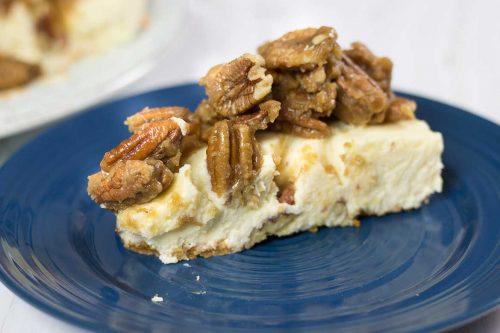 big slice of eggnog cheesecake topped with sugared pecans on a dark blue plate