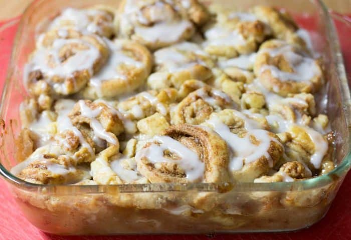Cinnamon Swirl Apple Cobbler with white sugar glaze in a square glass baking dish on a red placemat