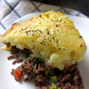 one serving of shepherd's pie on white plate, with whole pie in background on checked cloth