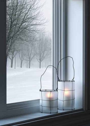 winter scene looking out a window you can see a snowstorm with two white candle holders, lit candles inside, and wrapped in wire with wire handles on the window sill.