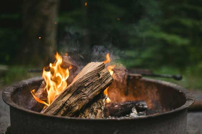 campfire in a metal truck tire ring, shows golden flames, with blurred out forest in the background