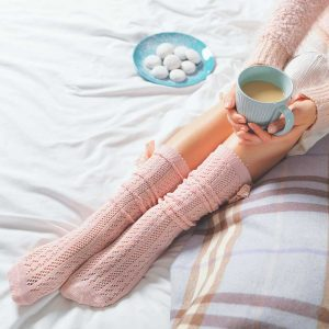 legs of woman with pink socks holding a blue mug of cocoa striped blanket and a blue plate of cookies